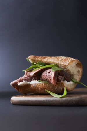 deli sanwdich with roast beef and rocket on dark background