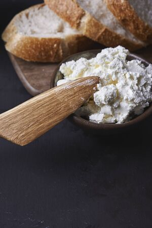 bowl cottage cheese with wooden knife  Stock Photo