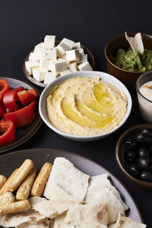 plate of hummus and vegetables, bread and dips on dark background