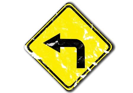 turn left: girare a sinistra grunge giallo traffico freccia segno dalle imbarcazioni da carta. Archivio Fotografico