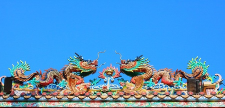 twin dragon on the roof with blue sky at Chinese shrine ,Thailand photo