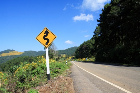 winding road sign, mountain background 스톡 콘텐츠