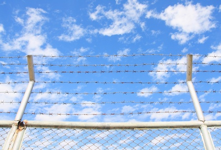 iron curtain: barbed wire on blue sky