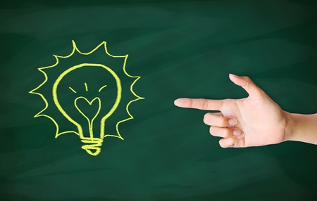 finger point to light bulb drawn on blackboard Stock Photo - 12854710