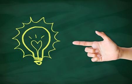 finger point to light bulb drawn on blackboard Stock Photo - 12854710