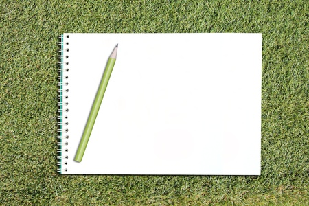 white notebook and pencil on grass background photo