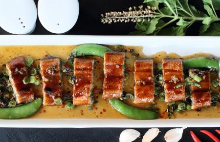 roast eel  unagi  with basil, Thai style fusion food  photo