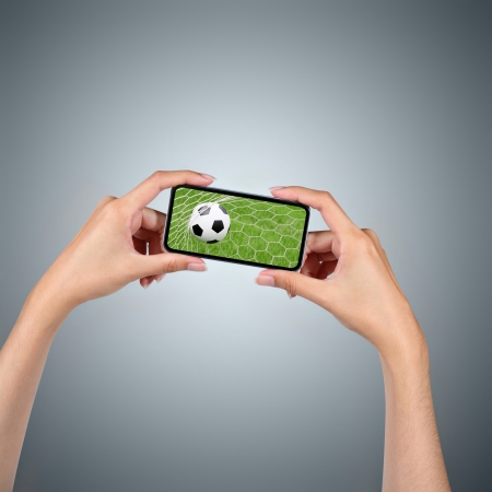 Hands holding smartphone with soccer ball background  photo