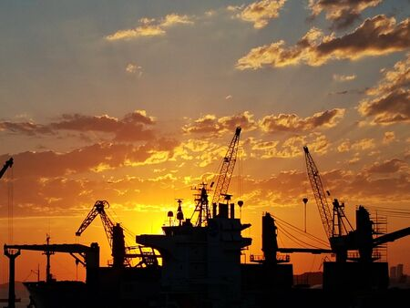 Sunset on a background of silhouettes from ship cranes arriving at the port. Editorial