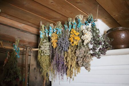 Meadow flowers of different varieties are suspended near the stove in a hut, to obtain dried flowers.