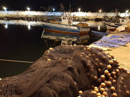 Small bots stand in the fishing port and the nets are dried on the pier. Skikda. Algeria. April 27, 2018. Sajtókép