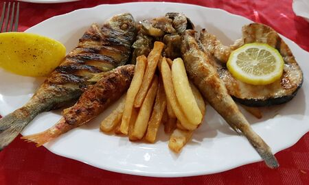 Fried several different river fish, with potatoes on a white plate.