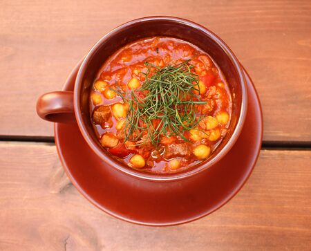 Tasty tomato soup with beans and dill in a ceramic bowl.
