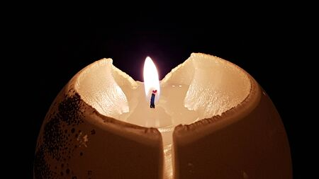 Semicircular burning candle on the table looks spectacular against a dark background.
