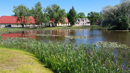 Houses and a reservoir overgrown along the shore with grass in the Latvian village of Kabile in May 2020. Editoriali