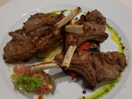 Lamb meat on the ribs cooked over a fire and served in a white plate for lunch Archivio Fotografico