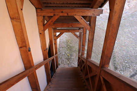 Wooden staircase leading from the second floor of the house to the courtyard of the utility yard