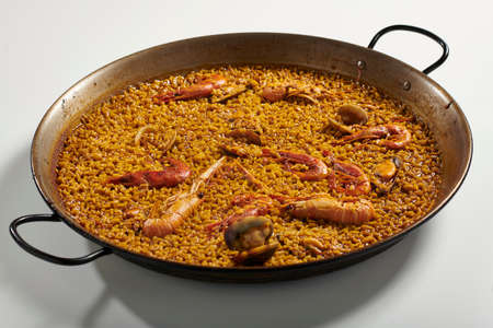 Traditional paella typical of Spain in traditional frying pan on white background