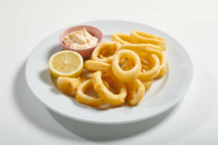 Plate of fried sliced ​​squid with mayonnaise sauce, lemon on white background