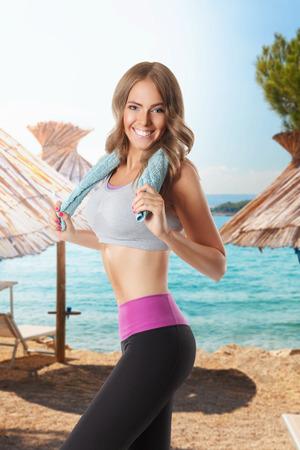 Fit mooie vrouw die op het strand