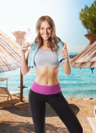 fit body: Smiling pretty woman doing the workout on the beach