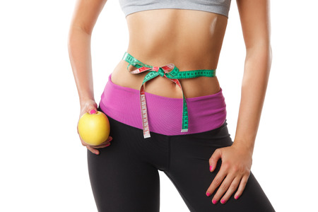 Closeup of a fit woman stomach with a tape measure Stock Photo