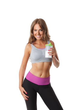 Fit pretty woman with a bottle of protein shakes isolated Stock Photo