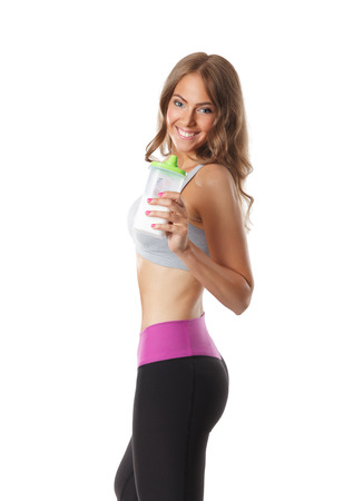 shake: Smiling pretty woman drinking a protein shake after workout