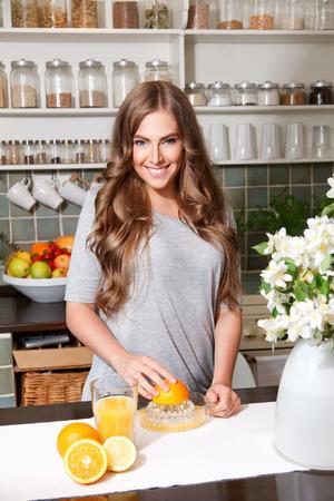 health woman: Pretty woman making fresh orange juice Stock Photo