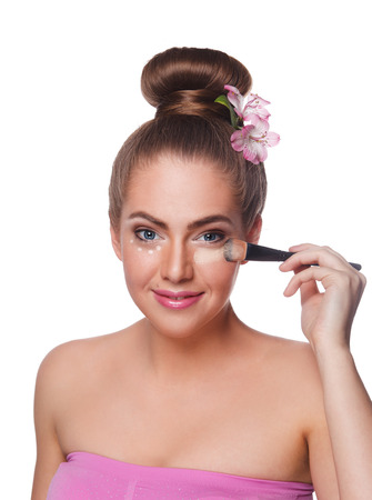 undereye: Beauty woman applying makeup concealer with a brush