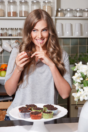 Woman on diet eating sweets in secret Stock Photo
