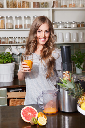 Pretty woman making juice with electric juicer