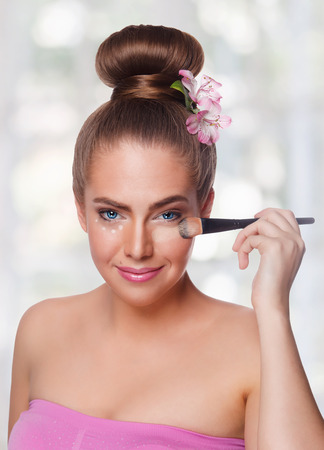 undereye: Beauty woman applying makeup concealer with brush