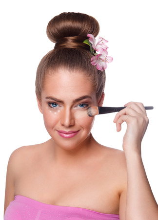 undereye: Pretty woman applying concealer with brush isolated on white Stock Photo