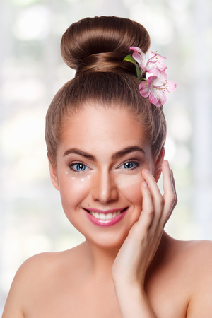 undereye: Beautiful woman applying concealer under eyes Stock Photo