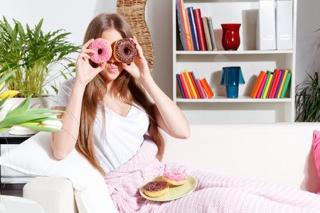 making fun: Woman making fun with delicious donuts Stock Photo