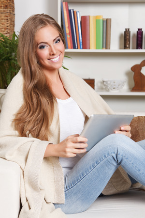 chilling: Happy woman holding a digital tablet