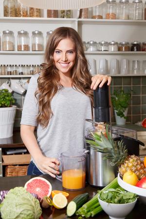 Mooie vrouw die een detox sap met een juicer Stockfoto