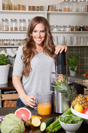 Pretty woman making a detox juice with a juicer