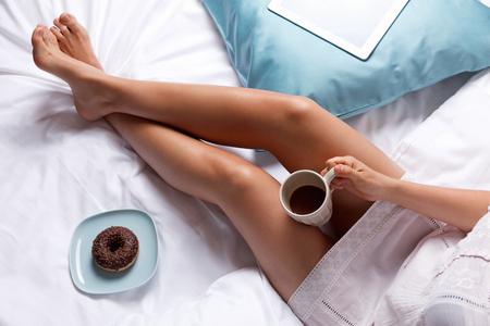 colazione: Donna che mangia ciambella e caffè per la colazione a letto Archivio Fotografico