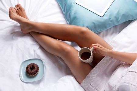 beds: Woman having donut and coffee for breakfast in the bed