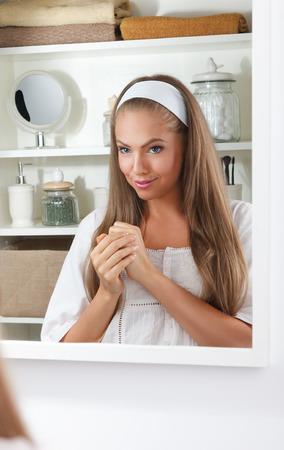 put: Pretty woman putting cream on her hand