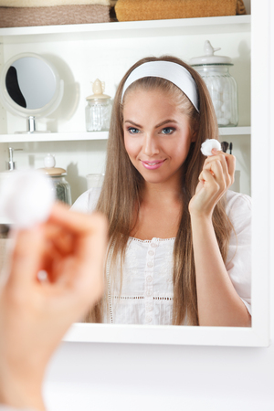 swab: Pretty woman using a cotton ball in the bathroom
