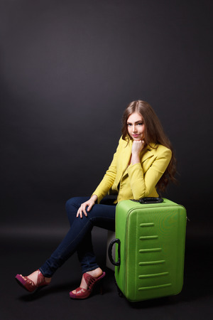 triplet: Pretty woman waiting with a suitcase Stock Photo