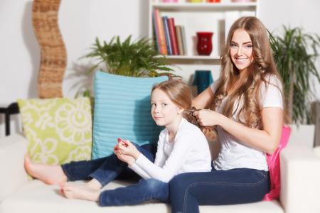 madre e hija: Madre bonita haciendo peinado de su hija Foto de archivo