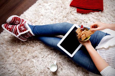 winter fashion: Woman with a tablet eating biscuits Stock Photo
