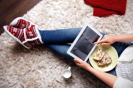 Vrouw met een tablet eten traditionele kerst cookies