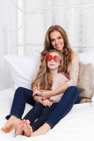 feel affection: Pretty mother and daughter in the bed