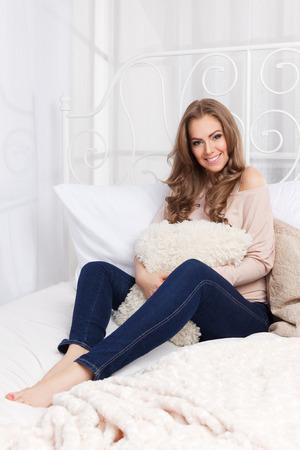ni�as sonriendo: Mujer bonita con una almohada abrazo en la cama