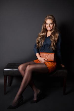 Mooie vrouw die een elegante envelop tas Stockfoto